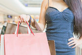 Closeup fashion woman holding big bags at shopping center — Stock Photo