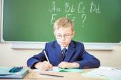 Schoolboy sits at a desk at school classroom — Stock Photo