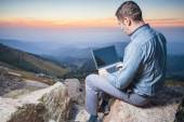 Image of a businessman on the top of the mountain, using a laptop — Stock Photo