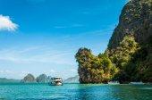 Motorboat docking alongside of the big limestone rock — Stock Photo