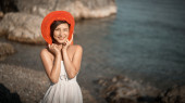 Hot beautiful woman in colorful sunhat and dress — Stock Photo