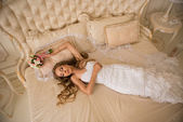 Charming beautiful bride holding wedding bouquet in her hands. bride in white dress in a luxury interiorlies on her back on the beautiful white bed. beautiful bride in a long white veil — Fotografia Stock
