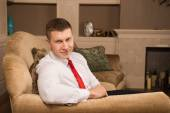 Successful handsome man sitting on the couch after work — Stock Photo