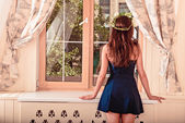 Girl looking out the window. girl turned her back.girl in a short dress. on beautiful hair is wreath — Foto de Stock