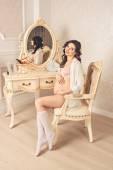 Happy pregnant in underwear sitting near mirror and stroking her tummy — Stock Photo