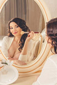 Beautiful girl doing makeup sitting in front of a mirror in underwear and dressing gown — Stock Photo