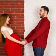 Young pregnant woman and her handsome husband hold hands and look at them. Pregnant girl in a red dress holding her belly. a young family on a red-white background — Stock Photo #71422871