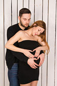 2 hearts formed with hands on the belly of a pregnant woman with twins. handsome man with his beautiful pregnant woman. man and woman looking at a big tummy — Stock Photo
