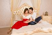 Young family expecting a baby. man and his pregnant woman sit on a big white bed — Stock Photo