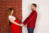 Young pregnant woman and her handsome husband hold hands and look at them. Pregnant girl in a red dress holding her belly. a young family on a red-white background — Stock Photo