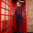 Beautiful young girl in casual style standing in a red telephone — Stock Photo #75974223