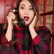 Beautiful young girl in casual style standing in a red telephone — Stock Photo #75974331