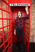Beautiful young girl in casual style standing in a red telephone — Stock Photo