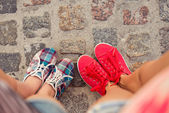 Top view of a two pairs of sneakers shoes walking on paving ston — Stock Photo