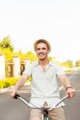 Happy young man in hat riding a bicycle — Stock Photo