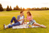 Cheers! Young man and woman at picnic — Stock Photo