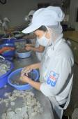 Quy Nhon, Vietnam - August 1, 2012: Workers are peeling fresh raw shrimps in a seafood factory in Quy Nhon city, Vietnam — Stock Photo