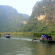 Ninh Binh, Vietnam - March 29, 2010: Ferrymen are taking tourists to visit the Trang An Eco-Tourism Complex, a complex beauty - landscapes called as an outdoor geological museum — Stock Photo #76678659