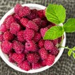 A plate full of fresh ripe raspberries with green leaf raspberry — Stock Photo #75956859