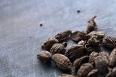 Seeds of black cardamom on the dark wooden table — Foto de Stock