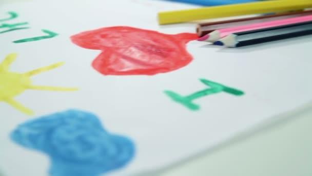 Niño dibuja pinturas sobre papel blanco — Vídeo de stock