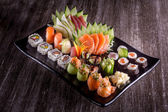 Sushi rolls on a plate with vegetables — Stock Photo