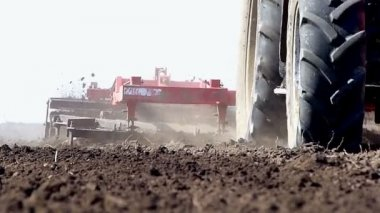 Tractor pulling land cultivating machine — Stockvideo