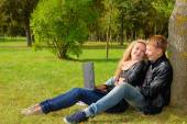 Teenage couple studying with a laptop in the park — Stock Photo