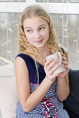 Girl sitting at the window with cup — Stock Photo