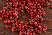Pink pepper on wooden table — Stock Photo