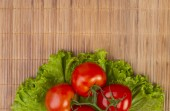 Tomatoes on lettuce leaves — Stock Photo