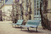 Romantic benches near the old house, where trees grow — Stock Photo