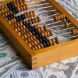 Old abacus on a pile of dollars — Stock Photo #78472238