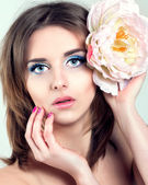 Beautiful Young Woman with Blue Eyes, Long Lashes and Pink nails. Flower in her Hair. — Stock Photo