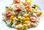 Couscous served with corns, zucchini and tomatoes — Stock Photo