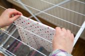 Woman hanging laundry to laundry stand — Stock Photo