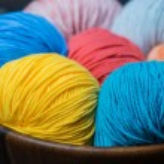 Colorful knitting yarn balls in basket — Stock Photo #70344013