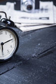 Black alarm clock with camera and newspaper on a wooden table — Stock Photo