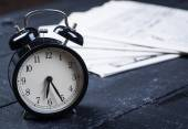 Black alarm clock with newspaper on a wooden table — Stock Photo