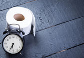 Alarm clock with toilet paper on a black wooden table — Stock Photo