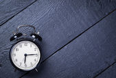 Alarm clock on a black wooden surface — Stock Photo