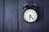 Alarm clock on a black wooden surface — Stockfoto
