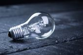 Tungsten bulb on a black wooden table — Stock Photo