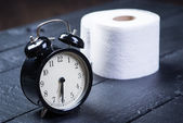 Alarm clock with toilet paper on a table — Stock Photo