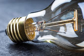 Tungsten bulb on a black table — Stock Photo