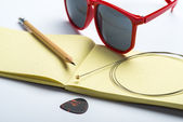 Yellow notepad with pencil, sunglasses, string and mediator on white surface — Stock Photo