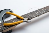 Guitar frets with string and yellow nippers — Stock Photo