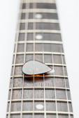 Guitar frets with strings and mediator — Stock Photo