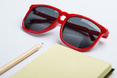 Red sunglasses with yellow notepad and pencil on white surface — Stock Photo