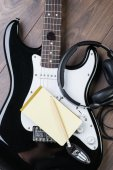 Electric guitar with headphones, notedpad and pencil on a brown wooden floor — Stock Photo